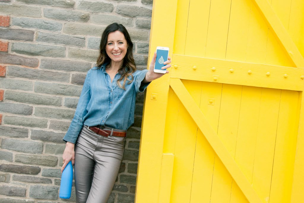 Women holding a cell phone in front of yellow door to celebrate Diags Shift app launch for job seekers