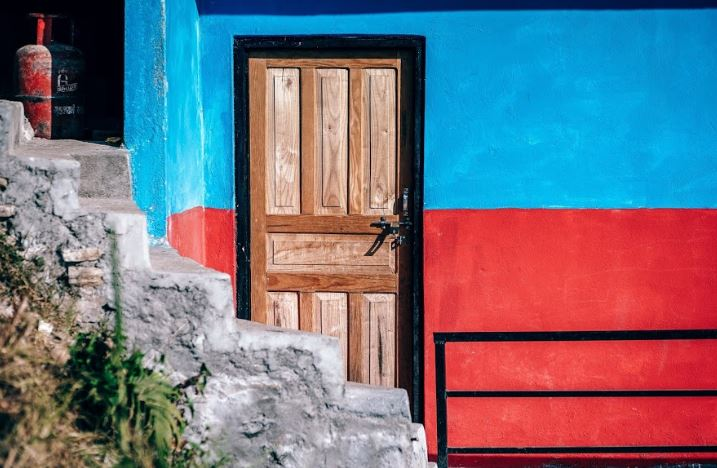 Bright red door on blue building depicting most important things a resume can not do for you