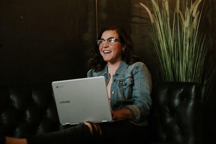 Gen Z employee smiling at her lap top depicting how recruitment marketing attracts gen zers