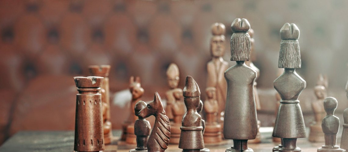 Brown leather chair table with chess board depicting strategic business case separating recruiting from HR