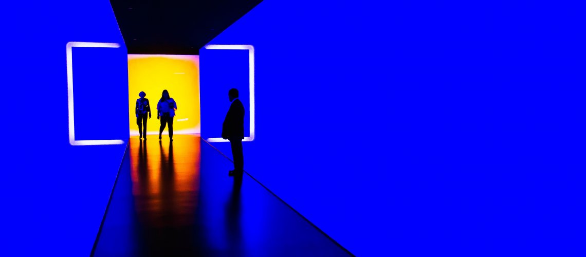 Blue hallway with silhouettes standing in an orange opening depicting way forward in evoloving recruiting model