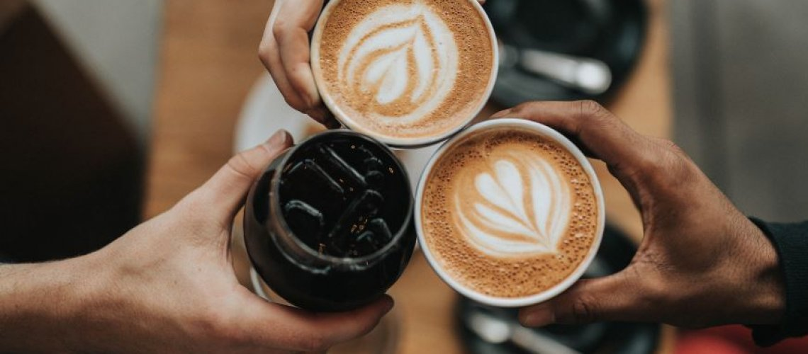 Hands doing cheers with coffee